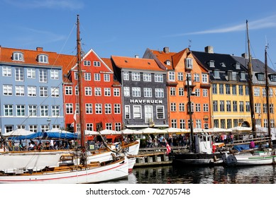 Copenhagen, Denmark - August 24, 2017: View of the Copenhagen restaurant district of Nyhavn with moored boats in the canal in front ofthe colorful buildings with restaurants.