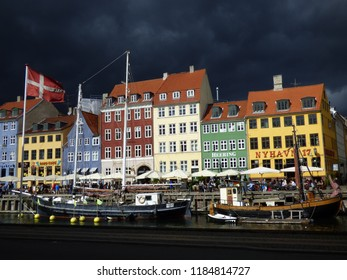 Copenhagen, Denmark. August 27 2016 Famous Nyhavn harbor, stormy sky, tourist attraction, vacation destination. Beautiful contrast between dark sky and colorful houses.