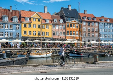 Copenhagen, Denmark - august 4, 2018: Sailing boats, classic houses and tourists on bicycles in the Nyhavn canal, in the historical and touristic center of the city