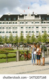 COPENHAGEN, DENMARK - AUGUST 9, 2019: Kongens Nytorv (The King's New Square) - public square in Copenhagen, Denmark. The Hotel D'Angleterre (England Hotel). Tourists with a map.