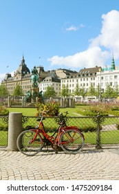 COPENHAGEN, DENMARK - AUGUST 9, 2019:Two women's  bikes stand on the sidewalk on the Kongens Nytorv (The King's New Square) is public square in Copenhagen, Denmark.The department store Magasin du Nord