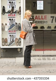 COPENHAGEN, DENMARK - CIRCA JUNE 2016: unidentified blonde fashion girl checking her mobile phone on the street