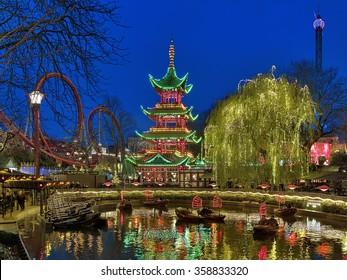 COPENHAGEN, DENMARK - DECEMBER 14, 2015: Evening view of Tivoli Gardens with Chinese pagoda, Dragon Boat lake and Daemonen roller coaster. Tivoli Gardens is the most-visited theme park in Scandinavia.