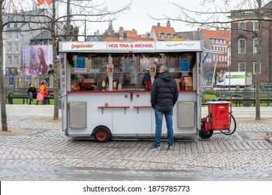 Copenhagen, Denmark - December 16, 2020: A man standing at a traditional hot dog cart in the city centre.