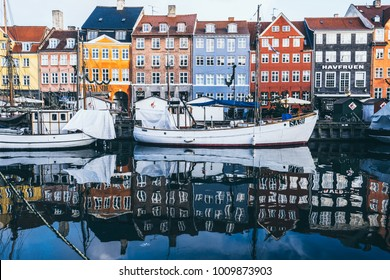 COPENHAGEN, DENMARK - DECEMBRE 2017: The Nyhavn port with boats and houses reflected in the water in morning winter light