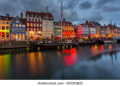 COPENHAGEN, DENMARK - FEBRUARY 28, 2017: Nyhavn at night. A 17th-century waterfront, canal and entertainment district with brightly colored townhouses, bars, pubs, restaurants and historical ships.