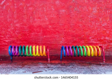 Copenhagen, Denmark - January 14, 2017: A rainbow colored bicycle rack in front of a red wall on the Red Square in Superkilen Park in Norrebro district.