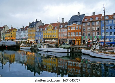 Copenhagen, Denmark - January 16, 2020 : Colourful houses and restaurants on Nyhavn Canal with old ships, Copenhagen.