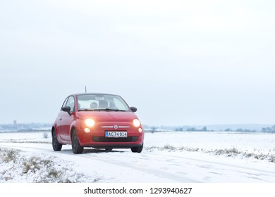 COPENHAGEN, DENMARK - JANUARY 24, 2019: Red Fiat 500 driving in the snow with a landscape in the background.