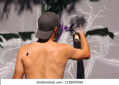 Copenhagen, Denmark - July 20, 2018: Street artist painting colorful graffiti on wall - Modern art concept with urban guy painting live murales with aerosol color spray in a sunny afternoon