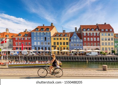 Copenhagen, Denmark - July, 2019: Copenhagen iconic view. Famous old Nyhavn port with colorful medieval houses, tourist ship and woman on a bicycle in the center of Copenhagen. Selective focus