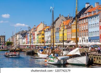 COPENHAGEN, DENMARK - JULY 25, 2014: Nyhavn district is one of the most famous landmark in Copenhagen. People enjoy sunny weather in open cafees in Copenhagen on July 25, 2014