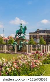 Copenhagen, Denmark - July 26 2019: Equestrian statue of Christian V in the centre of Kongens Nytorv Nyhavn Copenhagen Denmark with flower arrangements