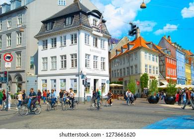 COPENHAGEN, DENMARK - JUNE 14, 2018: People walking and cycling at Copenhagen Old Town street. Copenhagen is the capital of Denmark