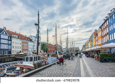 COPENHAGEN, DENMARK - JUNE 21, 2017: Nyhavn Pedestrian waterfront street: outdoor cafes and colorful buildings. Nyhavn (New Harbour) is XVII century waterfront, canal and entertainment district.