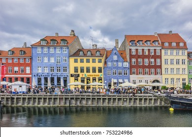 COPENHAGEN, DENMARK - JUNE 21, 2017: Nyhavn Pedestrian waterfront street: outdoor cafes & colorful buildings. Nyhavn (New Harbour) is XVII century waterfront, canal and entertainment district.