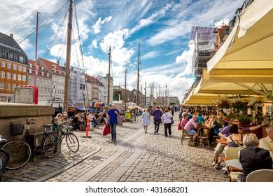 Copenhagen, Denmark - June 25th 2014 - Big group of locals and tourists enjoying a summer blue sky day in downtown Copenhagen in Denmark