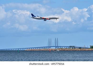 COPENHAGEN, DENMARK - JUNE 26, 2017: Airplane about to land in Copenhagen flying above Oresund Bridge with the landing gear down