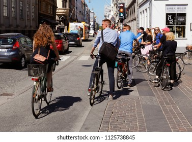 Copenhagen, Denmark - June 27, 2018: People on bicycles at the intersection with the streets Kongens nytorv and Bredgate in the downtown district waiting for green light.
