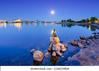 Copenhagen, Denmark - June 27, 2018: The Little Mermaid (Danish: Den lille Havfrue) by the waterside at the Langelinie promenade at night. It  is a bronze statue by Edvard Eriksen.