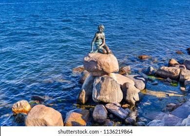 Copenhagen, Denmark - June 28, 2018: The Little Mermaid (Danish: Den lille Havfrue) on a rock by the waterside at the Langelinie promenade. It  is a bronze statue by Edvard Eriksen.