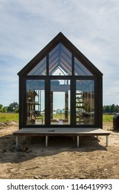 Copenhagen, Denmark - June 9 2018 : Beautifully designed one room, insulated 'transitional home', glass with steel frame, on display in an open field in Refshaleøen, Copenhagen