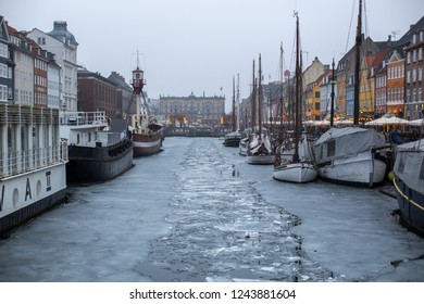 Copenhagen, Denmark - March 11, 2018: The famous Nyhavn pier with colourful buildings and boats on a frozen canal