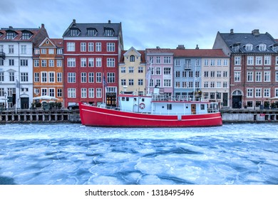 Copenhagen, Denmark - March 2, 2018: The famous Nyhavn pier with colourful buildings and a red boat on the frozen canal. Nyhavn is a waterfront, canal and entertainment district in Copenhagen.