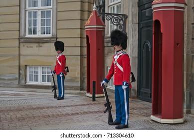Copenhagen, Denmark - March 28, 2017: The guards of honor in red gala uniform guarding the Royal residence Amalienborg Palace in Copenhagen, Denmark