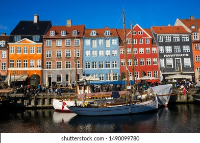 Copenhagen, Denmark - March 29, 2019: beautiful embankment, the so-called Nyhavn in the capital of Denmak, with colorful houses, boats hygge nearby restaurants and their reflections in the water of th