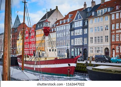 Copenhagen, Denmark - March 3 2018: Famous Nyhavn pier with colourful buildings and boats above a frozen canal in winter