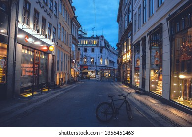 Copenhagen, Denmark - March 30, 2018: Lonely bike on Skoubogade street in cultural historical old town with shops and cafes under the evening blue sky with warm lights