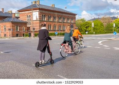 Copenhagen, Denmark - May 04, 2019: Young women riding on bicycles in Copenhagen old town, Denmark.