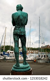 Copenhagen, Denmark - May 07 2007: Rear view of bronze statue on the background of yachts in the port