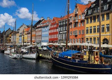 COPENHAGEN, DENMARK - May 13, 2019 : Colorful historical houses and old wooden boats located on the canal of famous Nyhavn port, on a sunny day