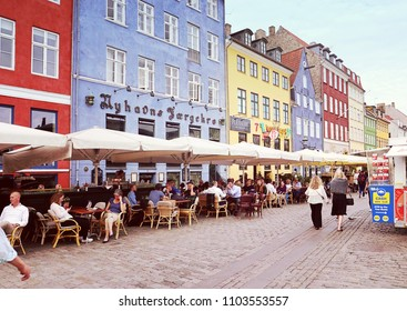 COPENHAGEN, DENMARK - MAY 15, 2018 Panoramic view of Nyhavn harbor waterfront with bars and restaurants,  famous touristic landmark and entertainment district of Copenhagen