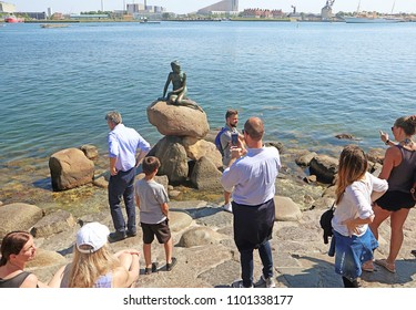 COPENHAGEN, DENMARK - MAY 16, 2018, tourists take pictures and selfies with the Little mermaid bronze statue symbol of the Danish capital inspired by the famous fairytale by Christian Andersen