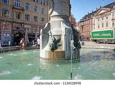COPENHAGEN, DENMARK - MAY 16, 2018 -Tourists take a refresh at Caritas well, fountain in Gammeltorv, the oldest fountain in Copenhagen built in 1608