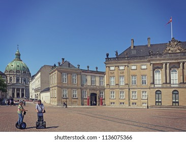 COPENHAGEN, DENMARK - MAY 16, 2018 Amalienborg Palace square, residence of the Danish Queen, with the Frederik's church (the Marble Church) and a couple of tourists visiting the city in segway