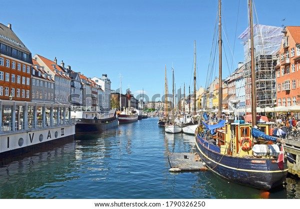 Copenhagen, Denmark - May 17 2014: a view of Nyhavn or New Harbor with tourists and residents enjoying the bars and restaurants alongside the waterway.