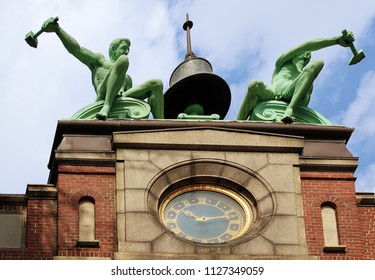 COPENHAGEN, DENMARK - MAY 18, 2018 The Ny Carlsberg Dipylon (double gate) building: the clock tower with the roof top bell flanked by the bronze fugures of the bell strikers by Stephan Sinding