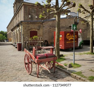 COPENHAGEN, DENMARK - MAY 18, 2018 the yard of the Old Carlsberg brewery in Copenhagen with with an old carriage in exposition and a Carlsberg beer distribution truck