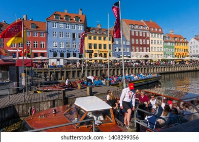 Copenhagen, Denmark - May 20, 2019: Tourists sightseeing cruising on boat by Nyhavn embankment, with colorful buildings in background in Copenhagen