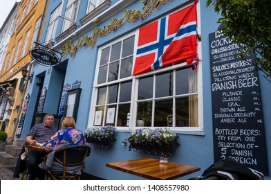 Copenhagen, Denmark - May 20, 2019:  Friends enjoying meal in outdoor restaurant at vintage old fashioned restaurant at famous Nyhavn pier in Copenhagen