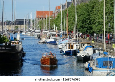COPENHAGEN, DENMARK, MAY 2017: Famous Nyhavn canal with rowhouses in sunny Copenhagen. Iconic row houses in waterfront district filled with locals and tourists sitting in restaurants, bars and cafes