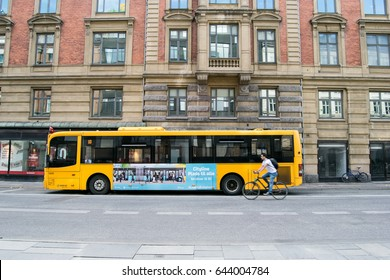 COPENHAGEN, DENMARK - MAY, 2017: Yellow bus and cyclist on a road in Copenhagen, Denmark.