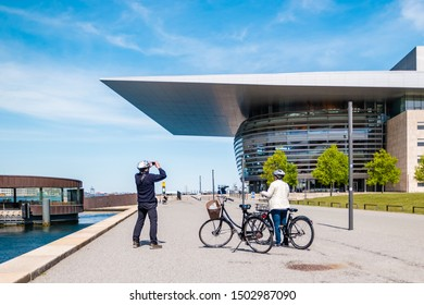 Copenhagen, Denmark - May, 2019: Two people with bicycles take pictures of Opera House in Copenhagen, Denmark.