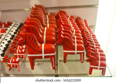 COPENHAGEN, DENMARK - May 25, 2019: Traditional wooden souvenirs from Denmark - red horses on display at a souvenir shop