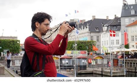 COPENHAGEN, DENMARK - MAY 31, 2017: photographer taking photos of The Nyhavn canal of Copenhagen with Den Franske Ambassade Militærmissionen Embassy of France on the background, Copenhagen, Denmark
