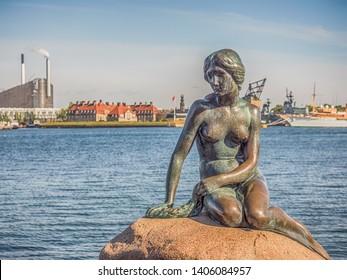 Copenhagen, Denmark - May 31, 2018: Bronze statue of the Little Mermaid, symbol of  Kopenhagen, Den lille Havfrue, on the coastal rocks, with nuclear power plant in the background